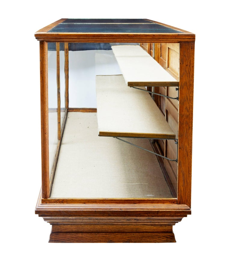 Fantastic haberdashery display cabinet of large proportions, circa 1910.  Glazed front, sides and top surfaces. Two adjustable shelves and base display area which is hessian covered.  To the back are 4 sliding doors which allows access to the