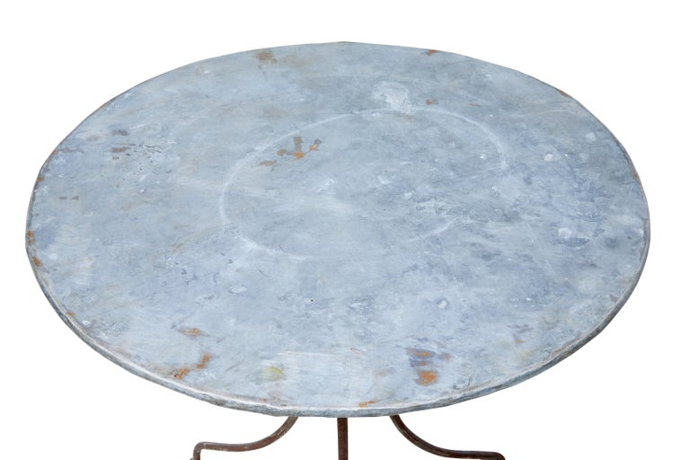 Good quality round metal occasional table from the 1920s.  Galvanised round top and steel shaped base. Ideal for use as a garden table or lamp table.  Traces of original paint to base, obvious signs of use to the top surface.