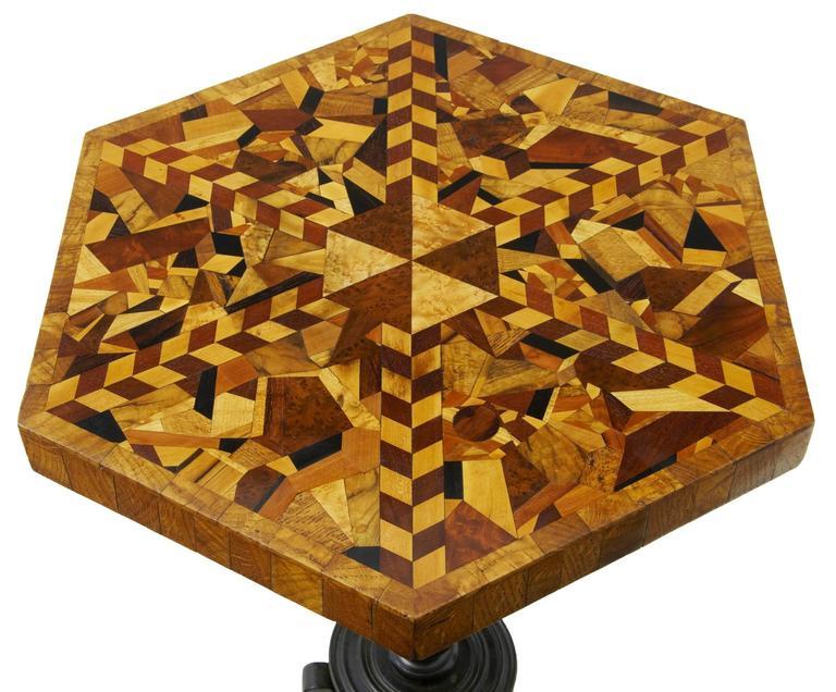 Unusual specimen wood table, circa 1840. Arranged specimens such as rosewood, oaks, ebony, walnut, boxwood, chestnut, elm, yew, mahogany, birch, cedar, beech and satinwood. Hexagonal shape with oak around the outside edge. Standing on turned