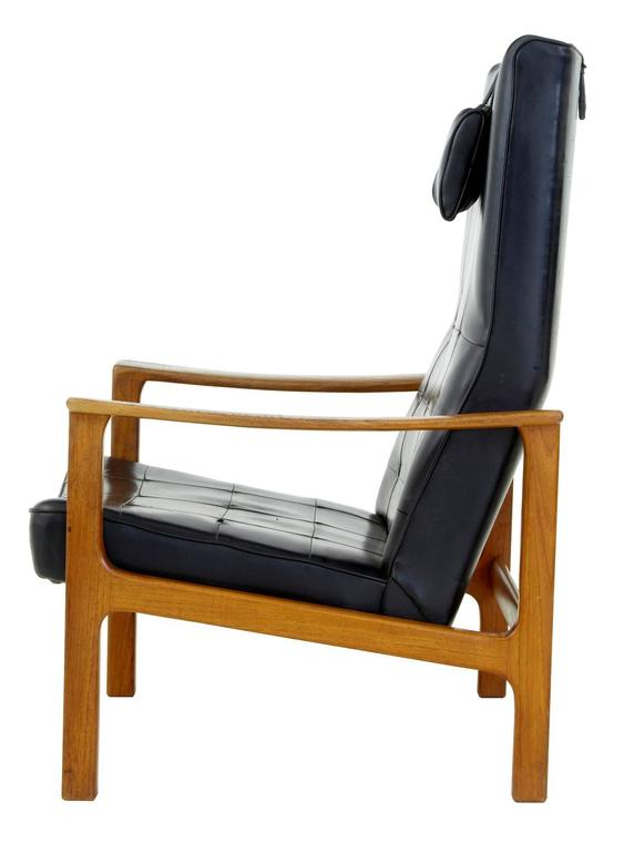 Fine piece of scandinavian design, circa 1960. Solid teak frame, with reclining capabilities. Black leather with squared piping. A few buttons missing to the back. Some pitting and scratch marks to leather on the seat and top of head