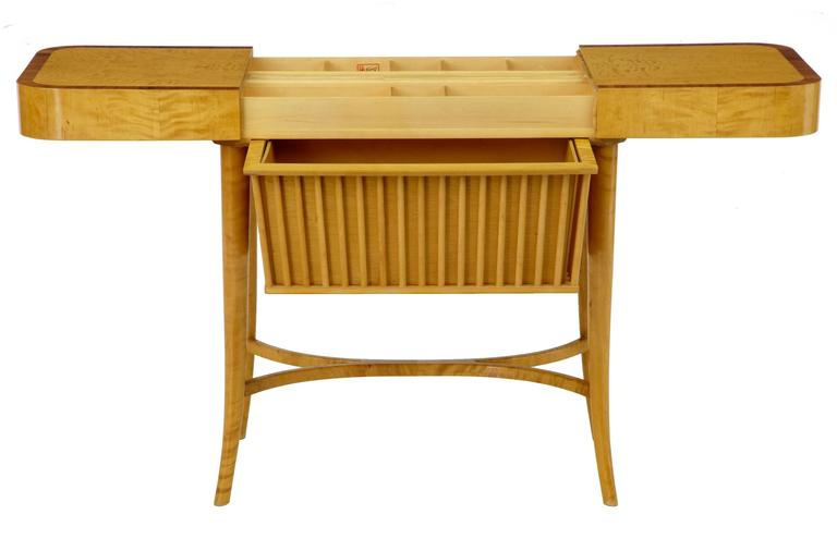 Superb quality work table by Bodafors of Sweden. Crossbanded with rosewood veneer around the top surface. Top surface separates to reveal fitted interior with compartments and spindles for cottons etc. pull-out storage drawer below. Legs united