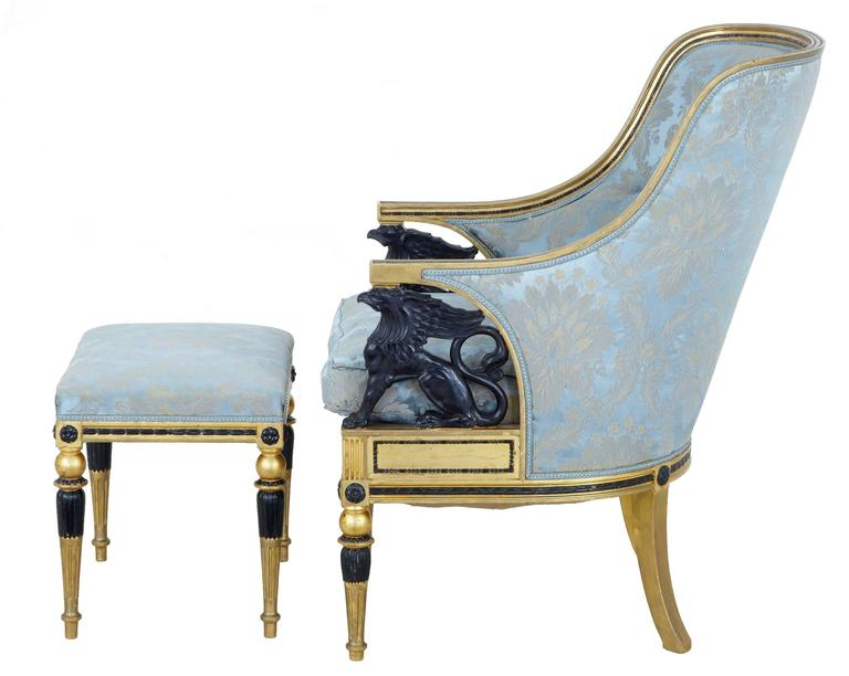 Fine quality Gothenburg gilt armchair and matching stool, circa 1870. Shaped backs with ebonized beading, which leads down to the ebonized carved griffins that form the support for the arm.  Silk fabric is clean and ready for immeadiate