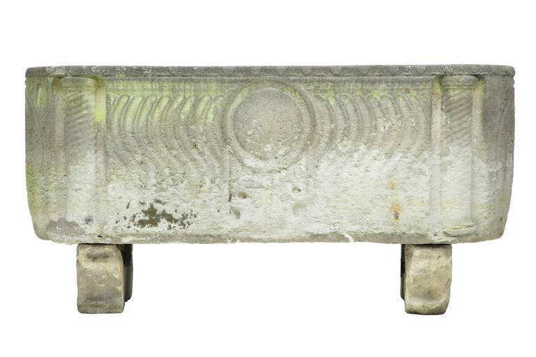 A stunning Anglo Roman sarcophagus in limestone, sitting on sledge feet and having curved strigilated side carvings with warrior shield and two crossed arrow symbols at each end. This unique piece was discovered in a Copenhagen garden. Although