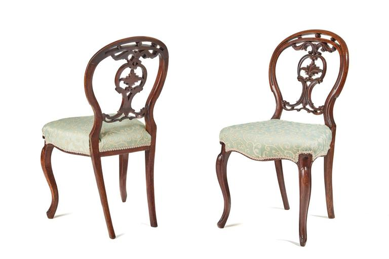 An elegant set of six Victorian walnut dining chairs, the balloon back having a nice carved centre, the seats are serpentine fronted and rest on a cabriole leg, the back legs are outswept these chairs have been newly re-upholstered.  Measures: