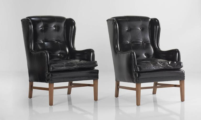Black Leather Wing Armchairs, circa 1950  Button back upholstery on walnut color birch frame.