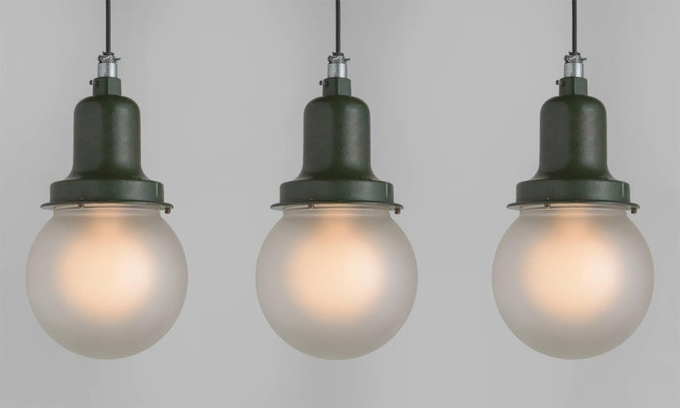 Westinghouse Explosion Proof Pendants, America, circa 1930  Westinghouse explosion proof pendants with original green paint and frosted globes. Industrial era American design with two-week lead time.  Overall height adjustable.