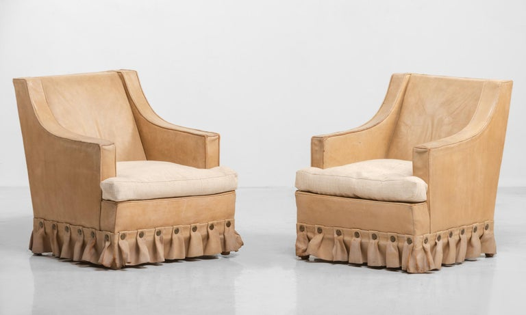 Pair of leather armchairs, circa 1960.  Original leather throughout includes a pleated skirt with large brass studs.