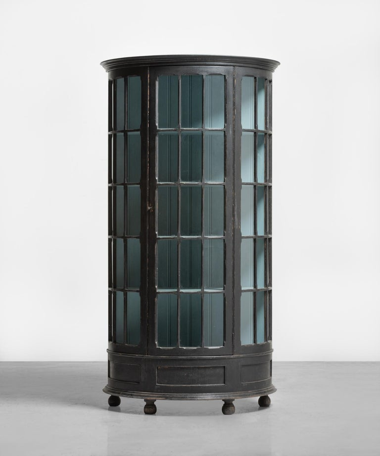 Demilune display cupboard, circa 1900  Unique form, with original ebonised finish on the exterior, and interior robins egg blue paint.