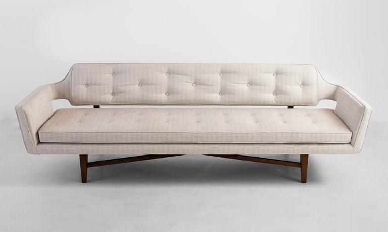 Model 6133 sofa by Edward Wormley, America, circa 1960.  Original upholstery with subtle tonal striping on cross bar wooden base.