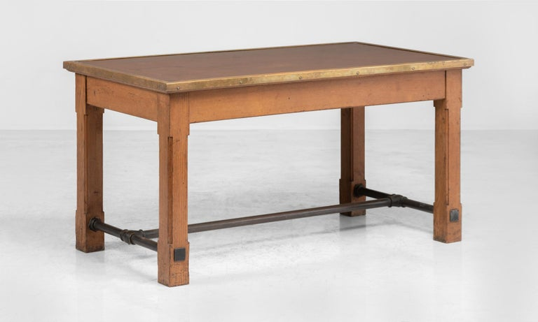 Oak, brass and leather bankers table, France, circa 1950.  A tabletop, inset with patinated leather and brass surround sits on a solid wooden base, with iron stretcher.  Measures: 59.5