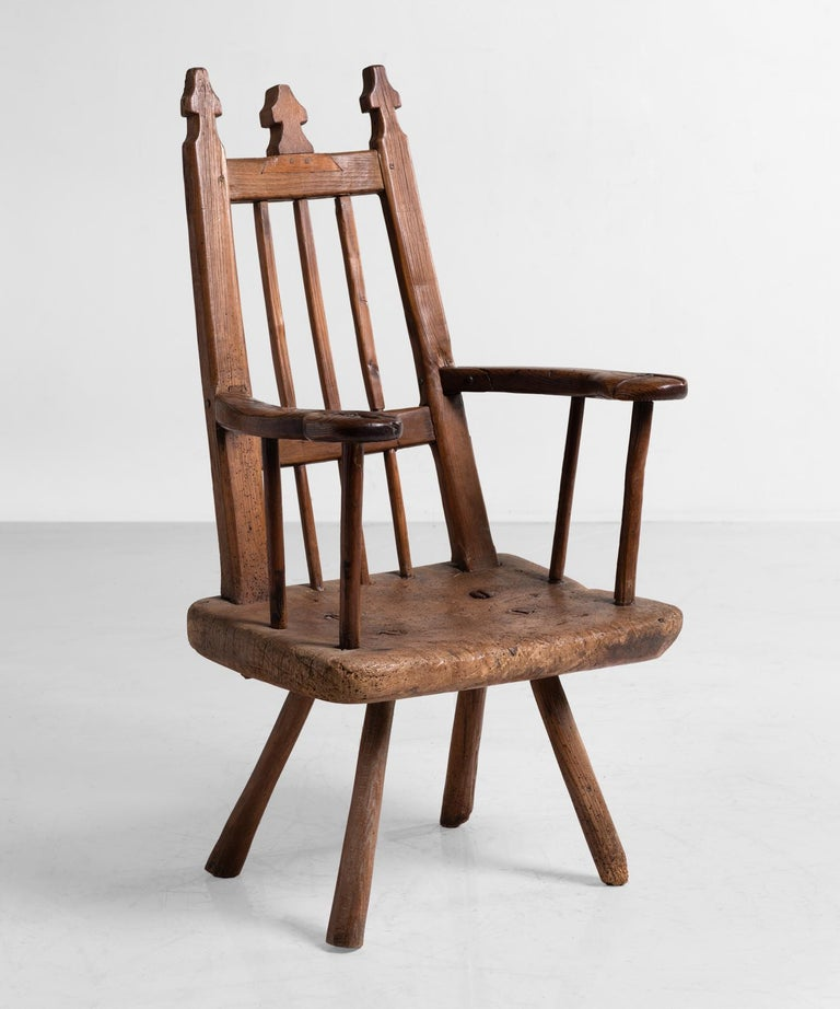 Primitive wooden armchair, England, circa 1820.  Unusual high back chair in ash and oak with shaped finials and six straight spindles on a slab seat.