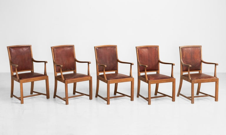 Carved oak and leather dining chairs, England, circa 1930.
