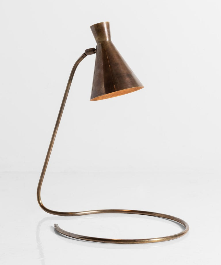 Brass modern table lamp, circa 1950  Beautifully patinated adjustable shade sits atop a slender arm, which coils into a circular base.