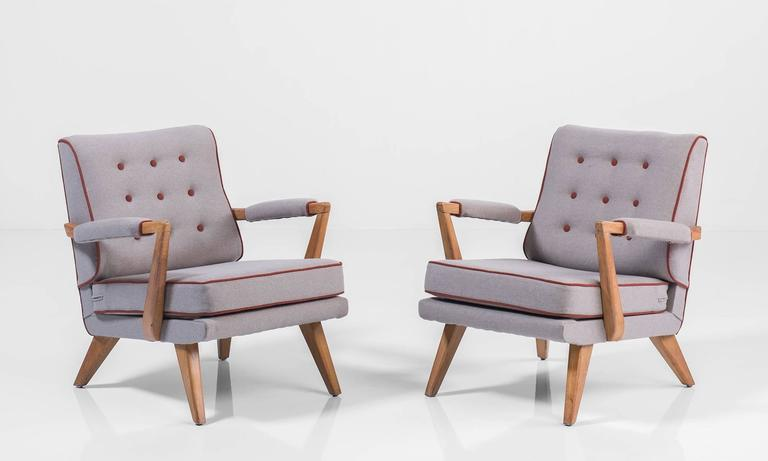 Upholstered modern oak armchairs, circa 1950.  With maroon piping. Elegant form with beautiful upholstery.