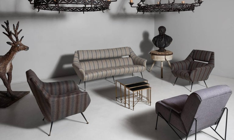 Open back wool sofa, Italy, circa 1960.  Newly reupholstered in striped wool maharam fabric, on black metal and brass feet.