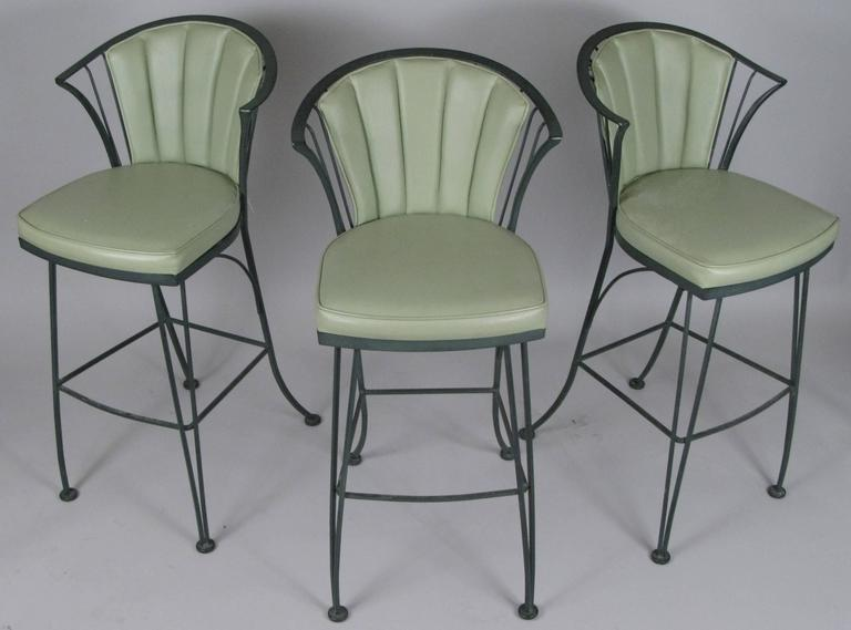 A set of three vintage 1960s wrought iron barstools from the Pinecrest collection by Woodard. Beautiful stylish design with curved legs and back and original seat and back cushions in green vinyl.