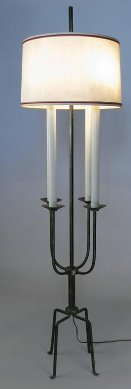 A classic modern 1940s wrought iron floor lamp by Tommi Parzinger for Parzinger originals. Beautiful design with four 'candle' lights and the original shade. In its original black with gold wash finish.