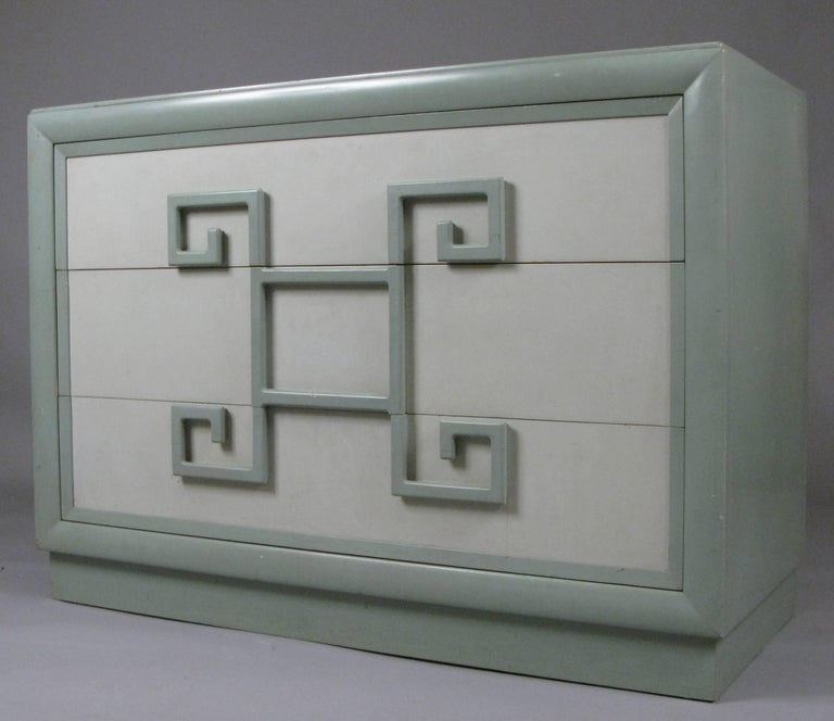 A Classic 1940s three-drawer chest by Kittinger. Their 'Mandarin' series is one of the most iconic from this era. The case has a wide molded trim and the drawers have unique Greek Key pulls. This chest is in its original pale green two tone finish,