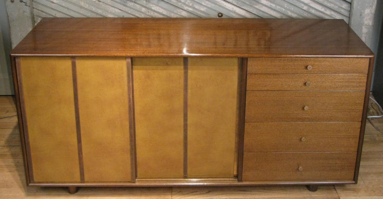 A very handsome 1950s cabinet chest designed by Harvey Probber, with a mahogany case and sliding leather doors covered in leather and brass trim. The sliding doors conceal shelves on the left and slide out mahogany trays on the right. The right side