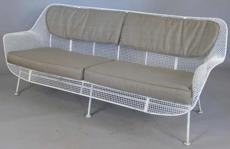 A set of Sculptura lounge seating by Russell Woodard, circa 1950. Set includes a long four seat sofa, and a pair of large lounge chairs with spring bases. Woodard's iconic Sculptura collection is designed with wrought iron frames and woven steel