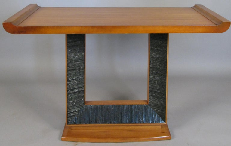 A beautiful 1940s console table designed by Paul Frankl for Brown Saltman, with a flared base, and open center section with ebonized combed detail border, and a wide top surface with raised ends.