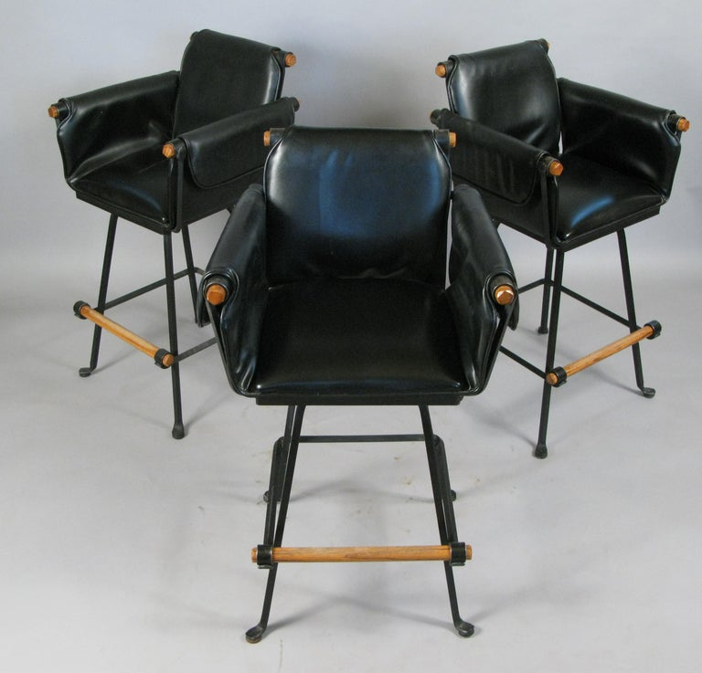 A beautiful set of three vintage 1970s swivel barstools with wrought iron frames and oak arms and footrests. With their original black vinyl upholstered seats and arms. Labeled Terra Furniture.