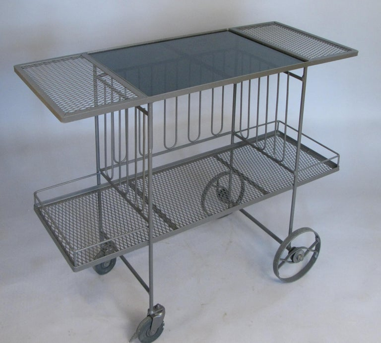 A very nice 1950s rolling bar cart in wrought iron with long vertical details around the center section, lower shelf with gallery rail, and a smoked black glass top, by Salterini.