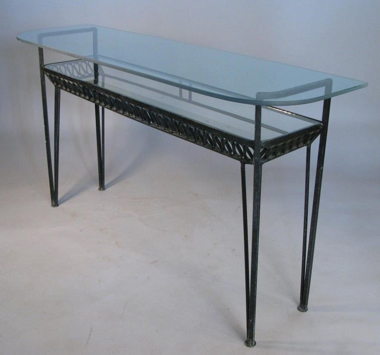A rare 1950s wrought iron double shelf console table designed by Maurizio Tempestini for Salterini, with two long glass shelves and Tempestini's signature iron ribbon design under the lower shelf.