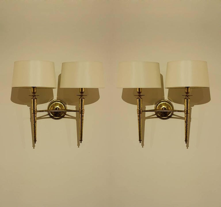 This elegant set of two pairs of brass sconces comes from a set of 1970 sconces we acquired from the Prince de Galles Hotel in Paris.  The sconce bodies are all in their original condition from 1940 and each have varying degrees of natural patina.