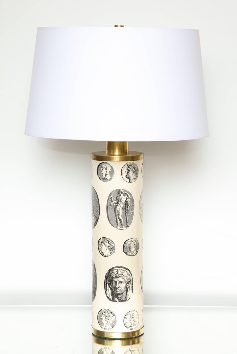 A fantastic pair of Fornasetti 'cameo' lamps in off white depicting Roman statuary and seals from 18th century illustrations. Shades included  however the shipping cost of shades is not  included 9
