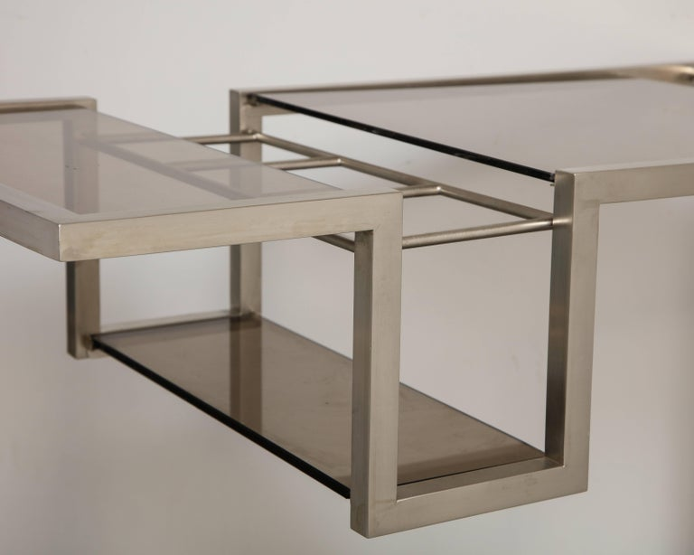 A stylish designer Italian brushed nickel cart with smoked glass shelves and bottle insert on easy rolling ball wheels possibly Romeo Rega.