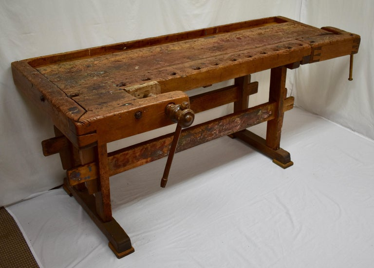 "This massive oak Joiner's workbench is built as solid as a rock and has been chopped, scraped, scratched and whacked through decades of purposeful use. The trestle-style base is made of pine and oak. The uprights are 2"" x 4"" boards of yellow pine,"