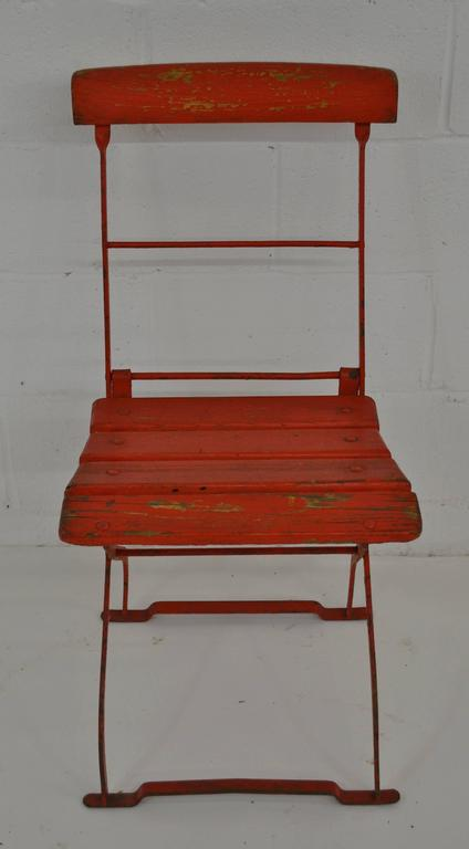 A wrought iron folding bistro chair with oak back rail and seat slats, by F. Schmidt of Elsterberg, Germany. In old very worn red paint on original green.