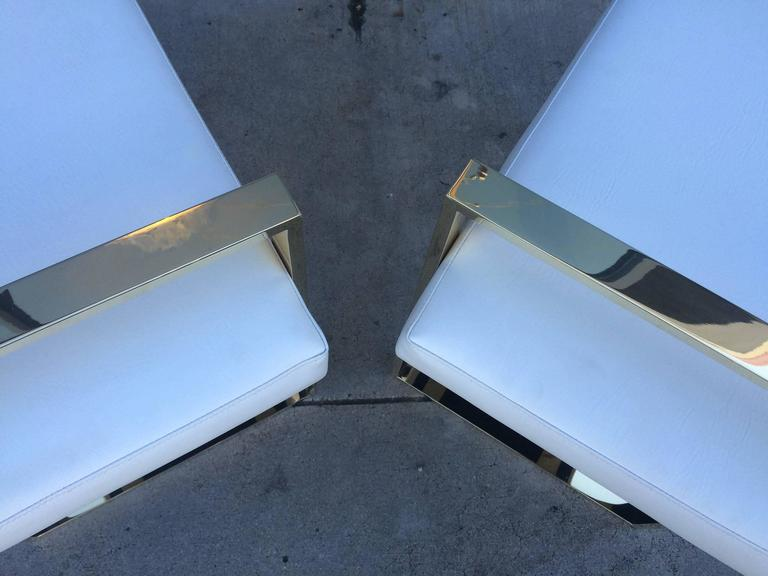 Pair of solid polished brass benches designed and manufactured by Charles Hollis Jones in the 1970s.  The frames of the benches are made in solid brass, they are upholstered in white Naugahyde but they are also available in other finishes such as