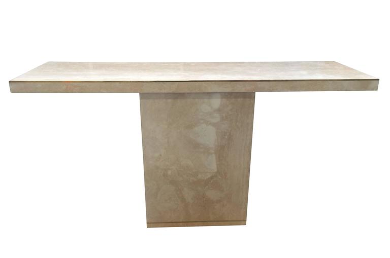 Stunning travertine and brass console designed and manufactured by Cain modern.  The travertine surface is absolutely breathtaking and the brass inlaid along the edges makes the piece really stand out. The table is made to order and we can