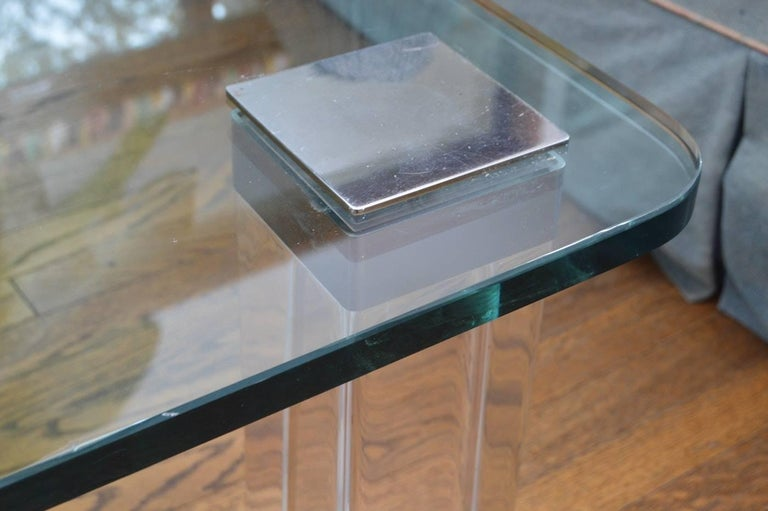Beautiful coffee table designed and manufactured in the 1970s and executed in Lucite and polished nickel with a nice glass top. The table has 3