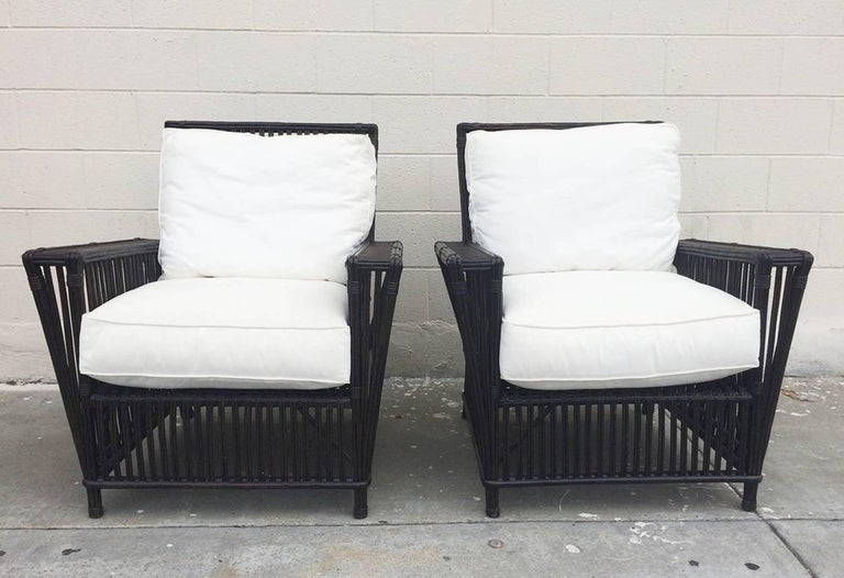 Beautiful pair of patio chairs made out of wicker or bamboo reeds and upholstered in white canvas fabric. The chairs are in excellent condition, the seats can be upholstered in COM or COL at no additional charge.  The chairs have great lines,