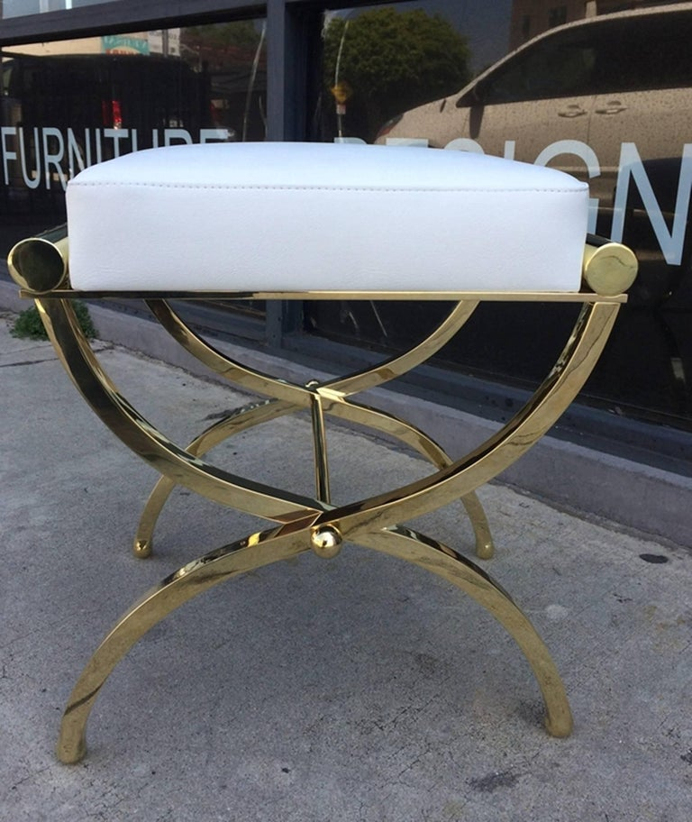 Exceptional pair of Empire style benches designed and manufactured by Charles Hollis Jones. The benches were designed in the 1960s and they are just as influential today.  The playful frames of these benches is made of solid brass with Lucite