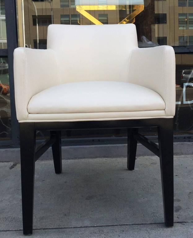 Stunning set of six dining armchairs possibly designed by Dunbar but labels are not found. The chairs are newly upholstered in a beautiful cream color vinyl fabric and the legs are refinished in a dark walnut stain.  The chairs are in excellent