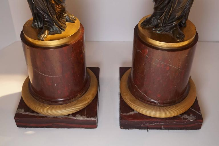 Pair of French Louis XVI style ormolu and patinated marble and bronze candelabra with figures holding three-arm candelabra in hand with rouge marble base having fantastic bronze casting with rooster head motif.