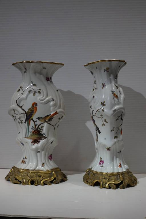 Pair of aesthetic painted porcelain and bronze covered urns with bird and flower decorations.