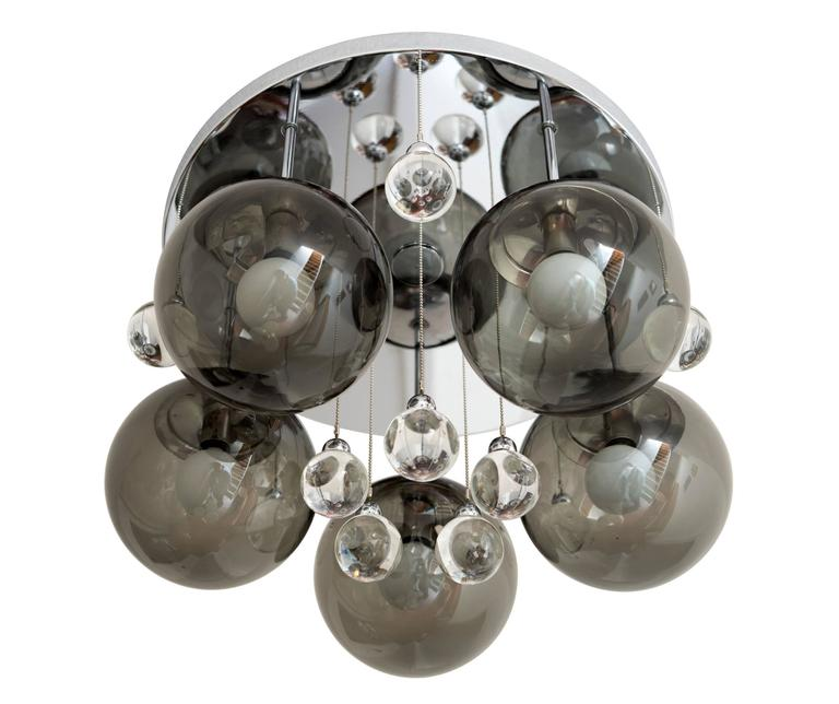 A striking pair of 1960s flush mount light fixtures or chandeliers with polished chrome frames, each supporting five pendant lights with smoked, blown glass shades and ten solid glass 'bubbles' with chrome mounts and suspended by ball chain. Signed