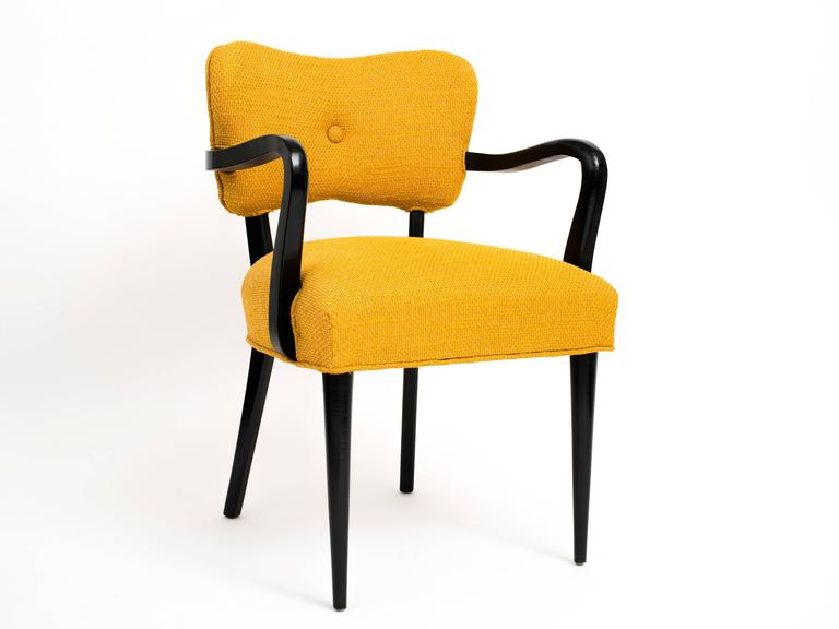 A timeless and well-built pair of modernist side chairs with ebonized, solid wood frames and with their original, creamsicle-colored wool upholstery. Rounded and tapered front legs against square rear legs, all being slightly flared which nicely