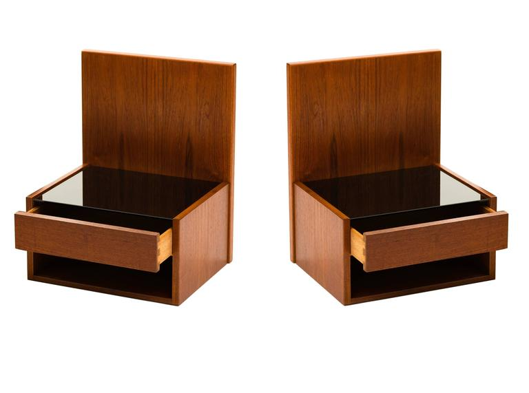 A pair of floating night stands or shelves in teak, each with a single drawer, open storage compartment beneath and a smoked glass top surface, designed by Hans Wegner for Getama. These may be mounted either to the wall or to the sides of your