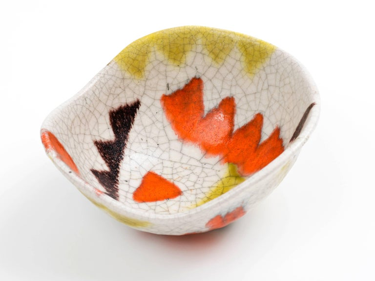 A freeform pottery bowl by Guido Gambone with applied triangular motif decoration in coral, eggplant, and ochre on an ivory ground. Lively tribal design with nice scale - - it's larger than it may appear in these images so please refer to