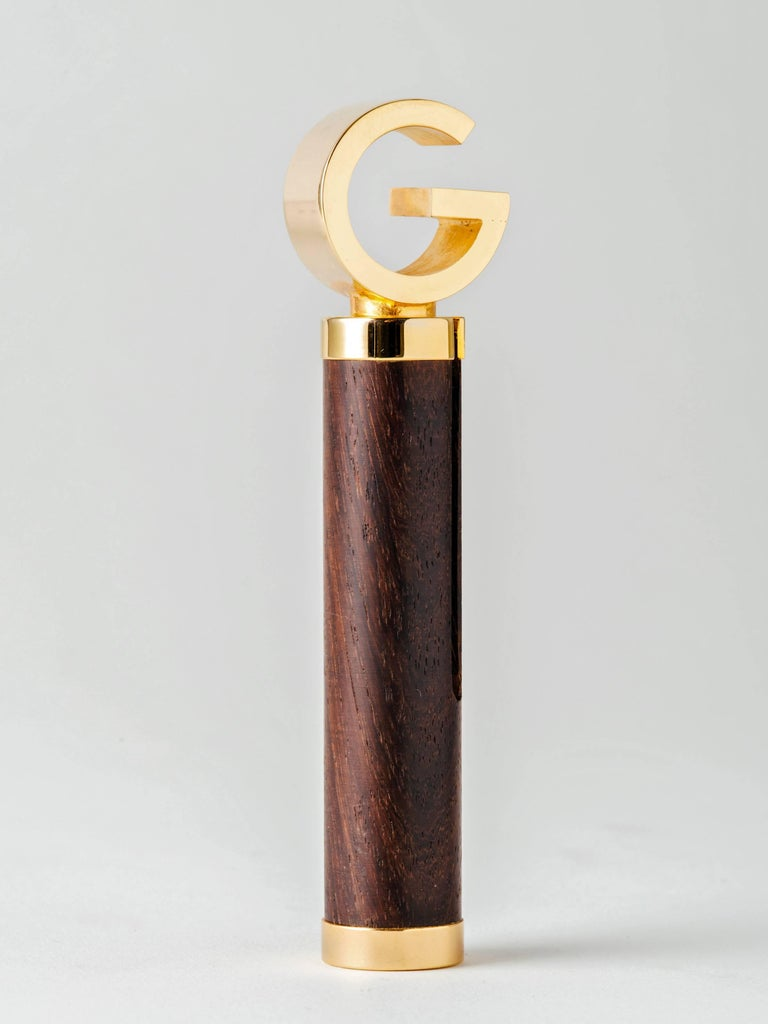 An ingeniously-designed, roundlet-style corkscrew or bottle opener executed in exotic wood and gold plated brass by Gucci, Italy, 1960s. The luxury brand's iconic G logo unscrews from the wood cylinder and slides precisely over one end to form a T