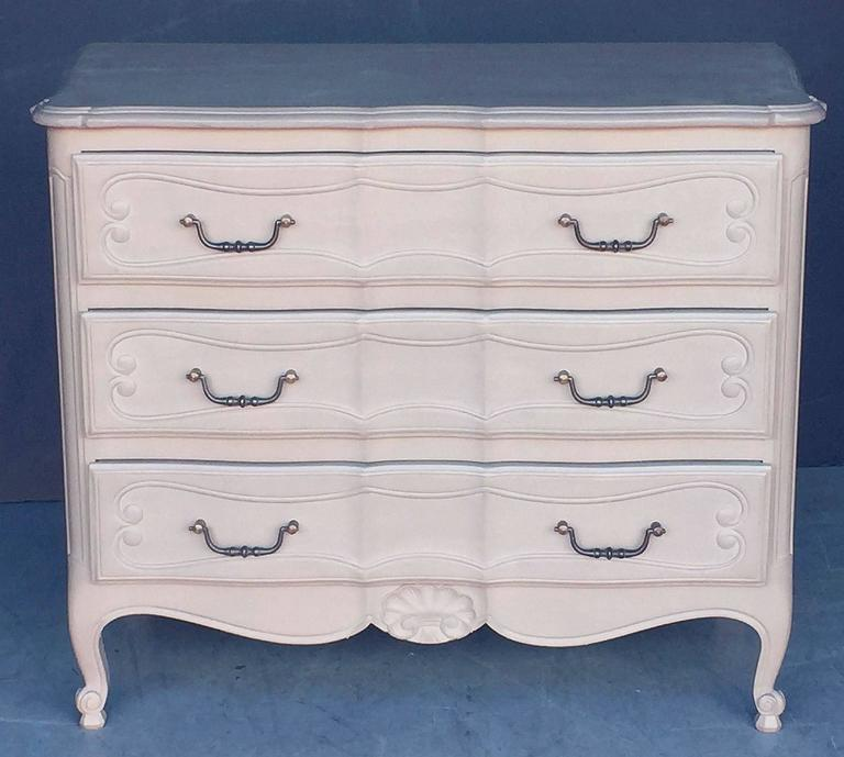 A fine French painted chest of drawers or commode, featuring a moulded top with serpentine edge, over a frieze of three drawers with paneled sides, each drawer with inset scroll design and swan handles, carved shell on the base and resting on facing