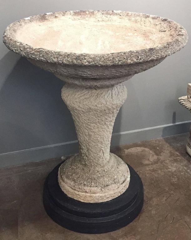 A large English decorative Planter on stand of composition stone, featuring a large flared round basin top, set upon a pedestal stand and optional round ebonized wooden base. Can be plugged for use as a bird bath.  An excellent addition to an indoor