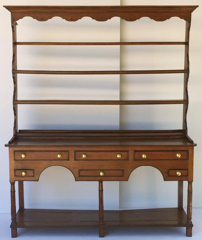 A handsome Welsh country pot board dresser of oak featuring a moulded crown top with ogee apron, over a plate rack with grooved plate rail and ogee sides.  Mounted to a dresser base frieze with five working drawers and one faux drawers, each