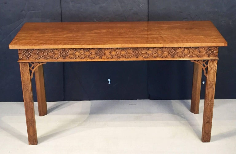 A fine English walnut console table or buffet server in the Chinese Chippendale style, featuring a figured walnut top over a carved fretwork frieze to the front and sides, on handsome carved canted supports, each leg with carved fretwork at the